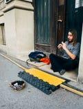 一个年轻人执行与在街道上的长笛仪器的,年轻人执行者 库存照片