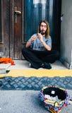 一个年轻人执行与在街道上的长笛仪器的,年轻人执行者 免版税库存图片