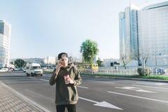 一个年轻人是谈话在电话和拿着一杯咖啡的学生,当走在城市附近时 生活方式和人们co 库存图片