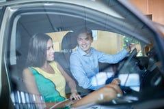 一个年轻人显示他的女朋友一辆新的汽车 买一辆新的汽车的概念 库存照片