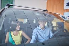 一个年轻人显示他的女朋友一辆新的汽车 买一辆新的汽车的概念 库存图片