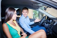 一个年轻人显示他的女朋友一辆新的汽车 买一辆新的汽车的概念 免版税库存照片