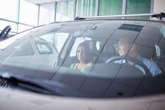 一个年轻人显示他的女朋友一辆新的汽车 买一辆新的汽车的概念 免版税库存图片
