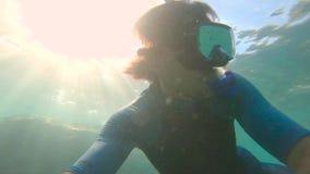 一个年轻人潜航的和潜水的垂度的慢动作射击到海里 U P 在衬衣的袖子的F 50 -表明 股票视频