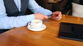 一个年轻人用聪明的电话和饮料咖啡,当坐在酒吧时 影视素材