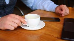 一个年轻人用聪明的电话和饮料咖啡,当坐在酒吧时 股票录像