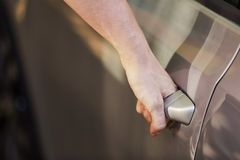 一个年轻人由把柄打开车门 免版税库存照片