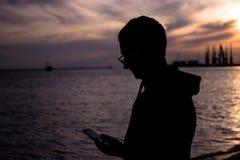 一个年轻人的剪影有一个电话的在美丽的日落天空的背景的手上由海的 免版税库存照片