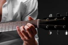 一个年轻人的手特写镜头弹在黑背景的吉他 乐器,艺术概念 库存图片