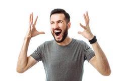 一个年轻人的特写镜头画象有胡子的,穿一件灰色T恤杉,当一个被激怒的表示,呼喊在愤怒,在t的手 免版税库存照片