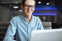 一个年轻人的画象以一种好心情,在衬衣的一个商人和玻璃,研究在咖啡馆的一台膝上型计算机,可以为a使用 库存图片