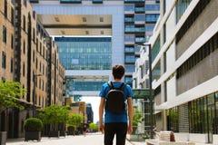 一个年轻人的背面图有背包的在大城市和看到达了对与透视的现代大厦 免版税库存照片