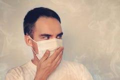 一个年轻人盖他的在面具的鼻子 难闻的气味恶臭,检疫的概念 烟覆盖 空气pollu的概念 免版税库存图片