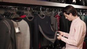 一个年轻人看一件毛线衣的材料在一个昂贵的精品店的 股票视频