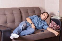 一个年轻人睡着了在长沙发,当看电视时 库存照片