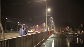一个年轻人穿过夜的欧洲城市走 影视素材