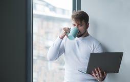 一个年轻人站立与膝上型计算机在窗口并且喝从杯子的咖啡 雇员工作在断裂 免版税库存照片