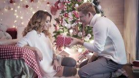 一个年轻人给一个圣诞节礼物坐在圣诞树附近的一个美丽的少妇 他们一起微笑 股票录像