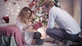 一个年轻人给一件礼物一名美丽的妇女在圣诞节 股票录像