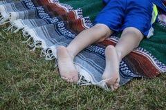 一个年轻人说谎的胃的赤脚和腿下来在草的一条被编织的毯子在一个室外音乐会 库存图片
