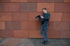 一个年轻人读一张报纸以橙色墙壁为背景 库存照片