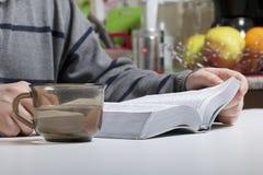 一个年轻人读与坐在桌上的一个银色切片的圣经 一个杯子用水是在它旁边 免版税库存照片