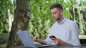 一个年轻人谈话在电话在公园 免版税库存图片