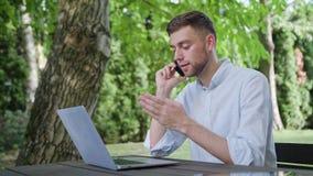 一个年轻人谈话在电话在公园 免版税库存照片