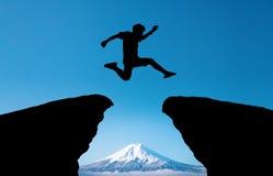 一个年轻人跳在山和通过在平衡五颜六色的天空的小山剪影空白 免版税库存图片
