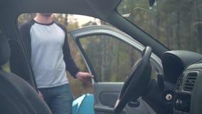 一个年轻人通过森林走,然后打开车门并且进入汽车 股票录像