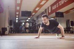 一个年轻人,俯卧撑锻炼,健身房地板, 免版税库存照片