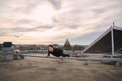 一个年轻人,户外在屋顶,都市城市屋顶,后边屋顶的锻炼, 免版税库存图片