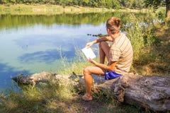 一个年轻人,有在河的河岸的一个笔记本的,湖,夏天认为在笔记本想法,山水画太阳的纪录 免版税库存照片