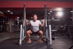 一个年轻人,杠铃后面蹲坐,室内黑暗的健身房 全长 免版税库存图片