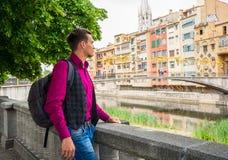 一个年轻人,游人,站立与在河岸O的一个背包 免版税图库摄影