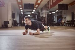 一个年轻人,看,板条锻炼,健身房地板, 免版税库存照片