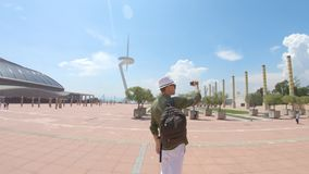 一个年轻人,站立与背包和在帽子和拍摄录影的游人由智能手机在Sant附近通讯台  影视素材