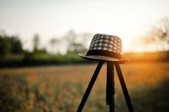 一个年轻人` s帽子在三脚架被安置 在的日落甚而 免版税库存图片