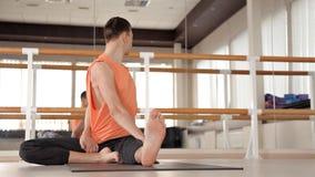一个年轻体育人参与Ashtanga瑜伽在演播室,有一个木地板和大镜子的 自由,健康和 影视素材