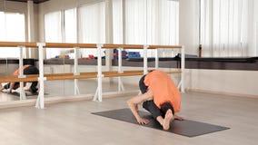 一个年轻体育人参与Ashtanga瑜伽在演播室,有一个木地板和大镜子的 自由,健康和 股票录像