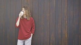 一个年轻偶然深色的女孩喝在木背景的咖啡 图库摄影