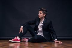 一个年轻十几岁的男孩,坐摆在模型 免版税图库摄影