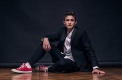 一个年轻十几岁的男孩,坐的摆在 图库摄影