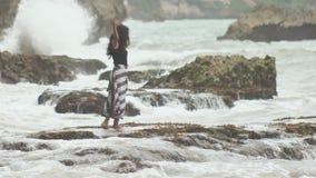 一个年轻印度尼西亚女孩是高兴的对在巴厘岛海岛的岩石岸的大波浪  股票录像