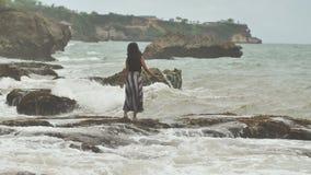 一个年轻印度尼西亚女孩是高兴的对在巴厘岛海岛的岩石岸的大波浪  股票视频