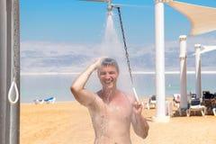 一个年轻可爱的人站立在海滩的一场阵雨下与浪花喷水在他附近和流动在赤裸的他的下 免版税库存照片