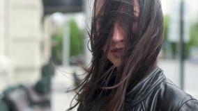一个年轻可爱的女孩的特写镜头画象 一阵强风用他的头发盖他的面孔 城市街道在背景中 影视素材