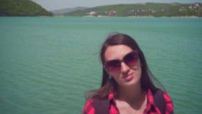 一个年轻可爱的女孩的画象一件红色方格的衬衣的,摆在照相机前面 影视素材