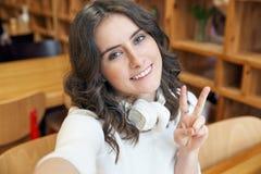 一个年轻可爱的学生女孩少年的自画象有宽微笑的在木咖啡馆内部背景  库存图片