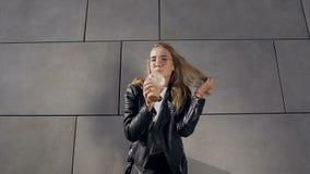 一个年轻可爱的金发碧眼的女人的都市画象女性在白色T恤和夹克饮用的奶昔通过秸杆  股票视频